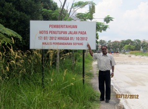 Councillor Santokh Singh pointing at the bill board stating the completion  of work is  01/10/2012