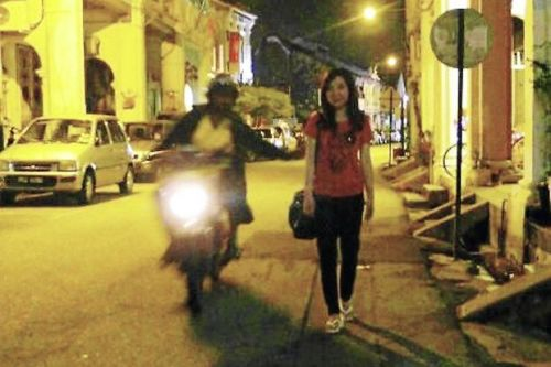 Caught in the act: The snatch thief attempting to grab Dai's handbag at Love Lane in Penang. (Right) The suspect being kept under close watch.